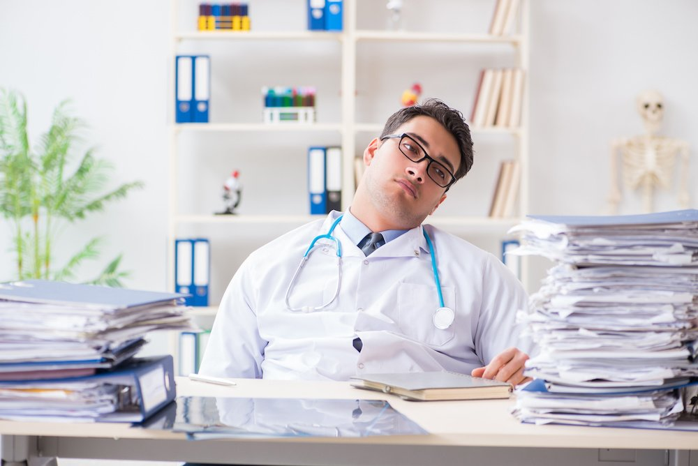 Busy doctor with too much work in hospital; blog: Why Outsourcing Medical Billing Services Might NOT Be Right for You